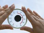 丸い温度計を持つ手