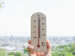 温度計を持つ手と町並