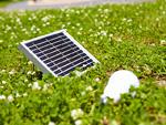 草原に置かれたソーラーパネルとLED電球