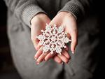 雪の結晶のオーナメントを持つ女性