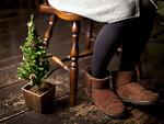 クリスマスツリーとムートンブーツを履いた女性の足元