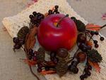 木の実のリースの中のリンゴ
