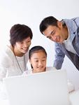 ノートパソコンを使う少女と両親
