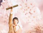 賞状筒を持った男子中学生と桜