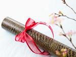 赤いリボンを結んだ賞状筒と桜