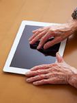 タブレットPCを触る90代女性の手