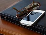 バインダー式ノートと眼鏡とスマートフォン