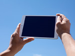 青空とタブレットPCを持つ手