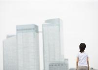 高層ビルと後ろ姿の女性