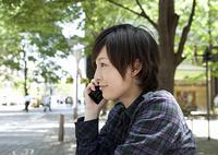 携帯電話をかける若い女性