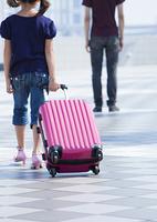 スーツケースを引く少女