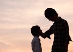 息子の頭を撫でる父親