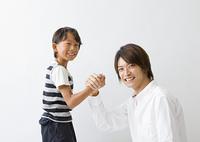 手を組む父と息子
