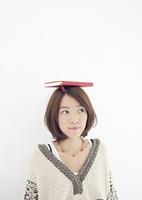 頭に本を乗せた若い女性