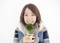 鉢植えを持つ若い女性