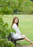 公園のベンチに座る若い女性