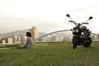 バイクと河川敷の女性