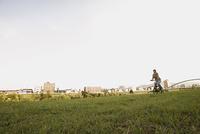 川原で自転車に乗る女性