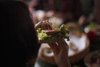 オープンサンドイッチを食べる女性