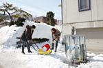 除雪するカップル