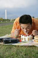 ケーキにかぶりつく男性