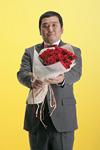 花束を持つスーツ姿の男性