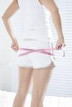 巻き尺でヒップを測る若い女性