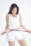 巻き尺でウエストを測る若い女性