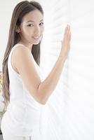 ブラインドに手をあてる若い女性