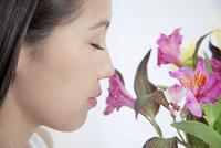 花のにおいを嗅ぐ若い女性