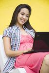 ベンチでノートパソコンを使う若い女性