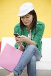 ベンチで携帯電話を使う若い女性