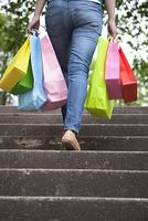 買い物袋を持って階段を上る女性