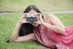 芝生に横たわってカメラで写真を撮る若い女性