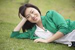 芝生に横たわる若い女性