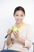 りんごの皮をむく若い女性