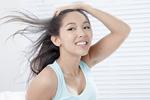 髪をかき上げる若い女性