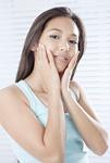 頬に手をあてる若い女性
