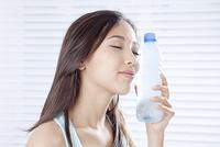 頬にペットボトルをあてる若い女性