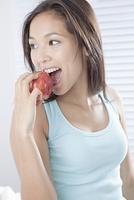 りんごをかじる若い女性