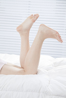 ベッドに横たわった女性の足