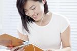 ノートを見ながら音楽を聴く若い女性
