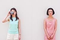 カメラを持つ女性と手を組む女性