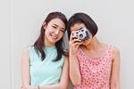 カメラを向ける女性と笑顔の女性
