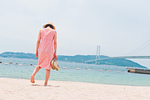 砂浜で歩く女性の後ろ姿