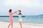 砂浜ではしゃぐ二人の女性