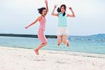 砂浜でジャンプする二人の女性