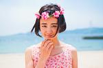 砂浜に立つ花かんむりをした女性