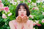 手のひらに花をのせる女性