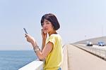 橋の上で音楽を聴く女性